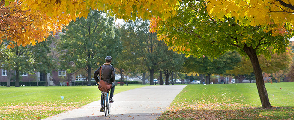student riding bicycle in Fall on Illinois quad